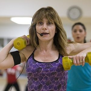 A female fitness instructor leads a class while holding small dumbells