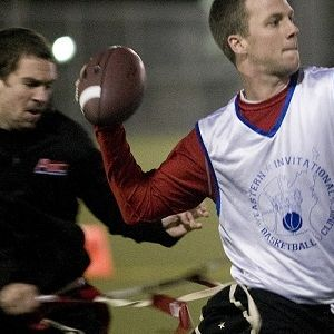 Quarterback preparing to throw the football while his flag gets pulled off behind him