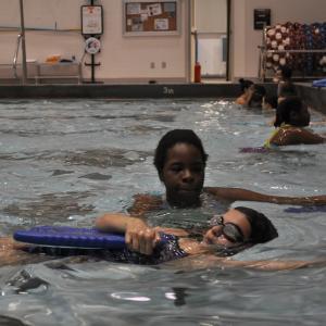 lifeguard teaching someone how to swim