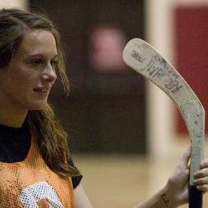 female holding hockey stick
