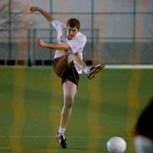 male kicking a soccer ball