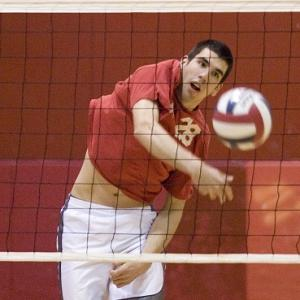 male hitting a volleyball