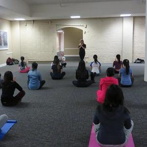 Students sit in lines and follow the directions of the yoga instructor leading them