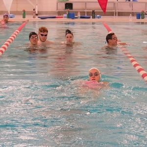 Students swim in a lane together