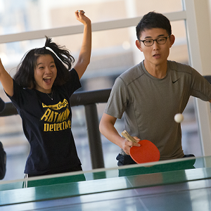 A girl cheers beside a boy who is playing table tennis.