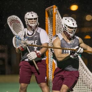 two males playing lacrosse
