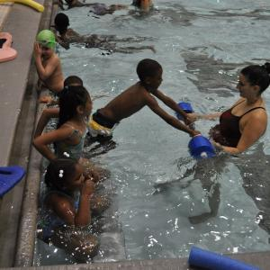 children learning to swim with instructor