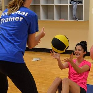 a personal fitness trainer and participant throw a ball back and forth