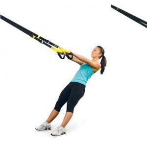 Woman using TRX resistance equipment.