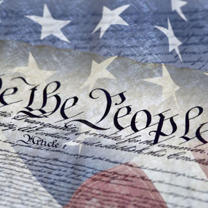Text from the Constitution printed over the American flag