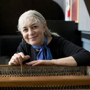 Woman with white hair and black sweater seated at harpsichord