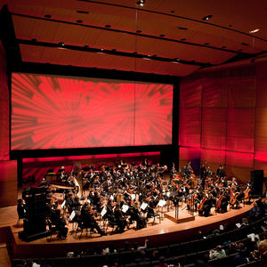 Large orchestral ensemble on stage with red lighting
