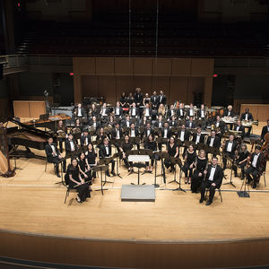 A band of roughly 75 musicians in a formal pose on stage in Temple Performing Arts Center