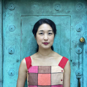 Korean musician gamin stands in front of a blue door