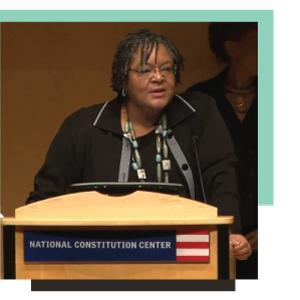 Maida Odom talking at a podium