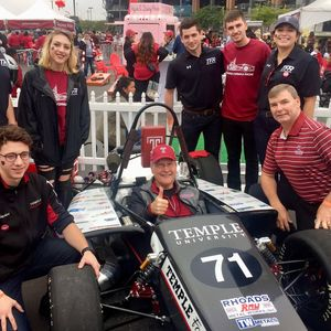 students and faculty with race car