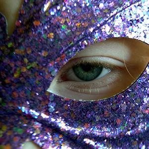Eye looking through a glitter mask
