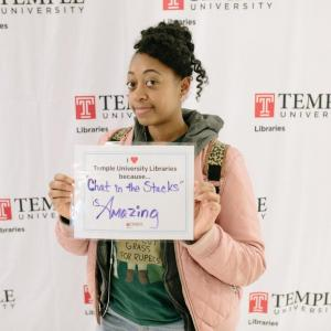 "photo of Temple student with sign that reads: ""I love the Libraries because 'Chat in the Stacks' is amazing."