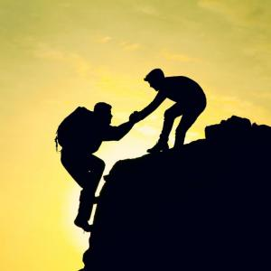 Two people climbing a mountain, one is helping the other one to the top.