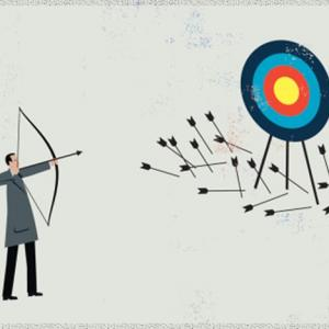 A man shooting arrows at a target with a bunch of arrows laying on the ground by the target