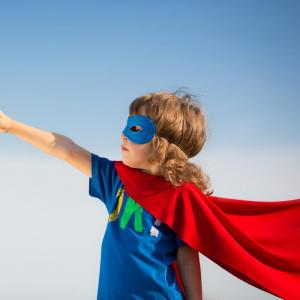 A boy dressed up as a superhero in a cape and mask.