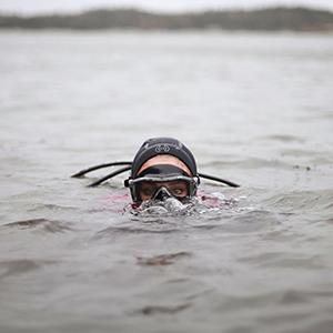 """Scuba diver with just her eyes above water in a still from Hope Ginsburgs """"Breathing on Land: Bay of Fundy"""""""
