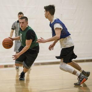A basketball player attempts to dribble around his defender while a ref watches in the background of the photo.
