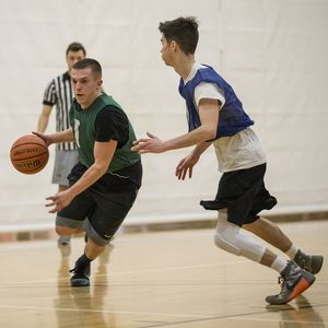 A basketball player tries to dribble around his defender while a ref watches in the background.