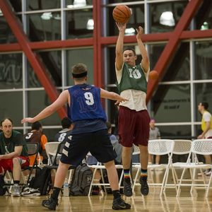 An intramural player shooting a 3 point shot while a player from the other team defends them.