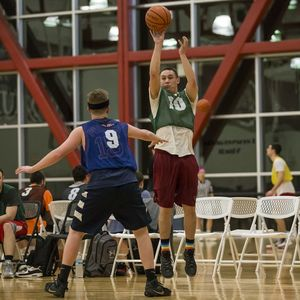 An intramural basketball player shoots a 3 point shot over the defender guarding him.