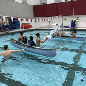 Two teams in canoes throw buckets of water at each other in an attempt to sink their opponents canoe.