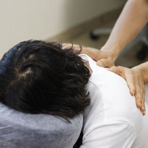 An individual in a white t-shirt gets a massage while sitting in a massage chair.