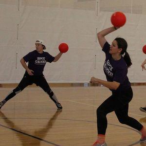 Teammates preparing to throw dodgeballs.