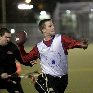 A flag football QB throwing the ball as a defender tries to pull his flag.