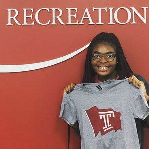 A student staff member holding up one of the Campus Rec Flag T-Shirts.