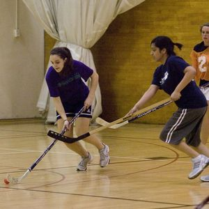 A female patron controlling the ball up the court in a game of Floor Hockey.