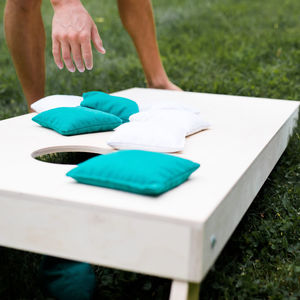 A photo of a cornhole board with bean bags sitting on it.