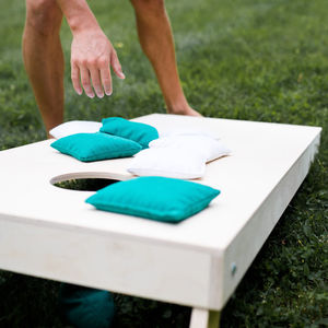 A picture of an intramural corn hole board with bean bags sitting on it.