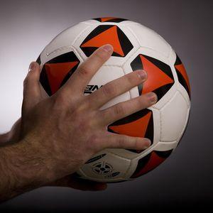 Hands holding a soccer ball.