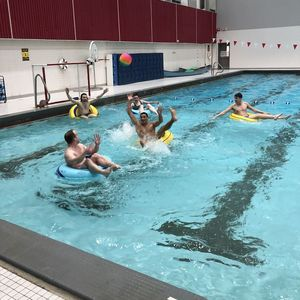 An inner-tube water polo player reaches to catch a pass that was thrown over the top of the defense.