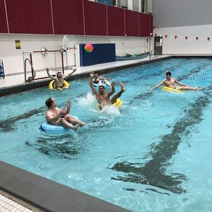 An Inner Tube Water Polo player reaches for a pass that is being thrown to them over the top of the defenders.