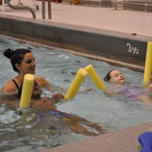 A swim instructor oversees two children in the pool with flotation noodles.
