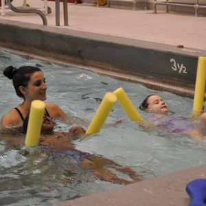 Two kids swimming with noodles as a swim instructor watches them.