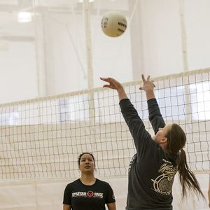 A volleyball players setting up the ball for a teammate next to the net.