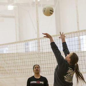 A player setting a volleyball for a teammate.