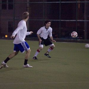 Players playing soccer at night on a turf field.