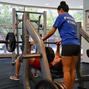 A personal trainer spots a client who is bench pressing.