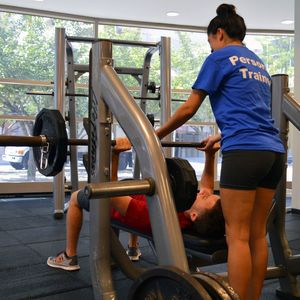A Personal Trainer watching a client lifting.