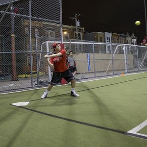 A batter preparing to swing at an incoming softball pitch.