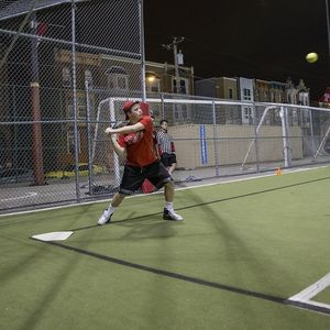 A batter preparing to swing at an incoming pitch.